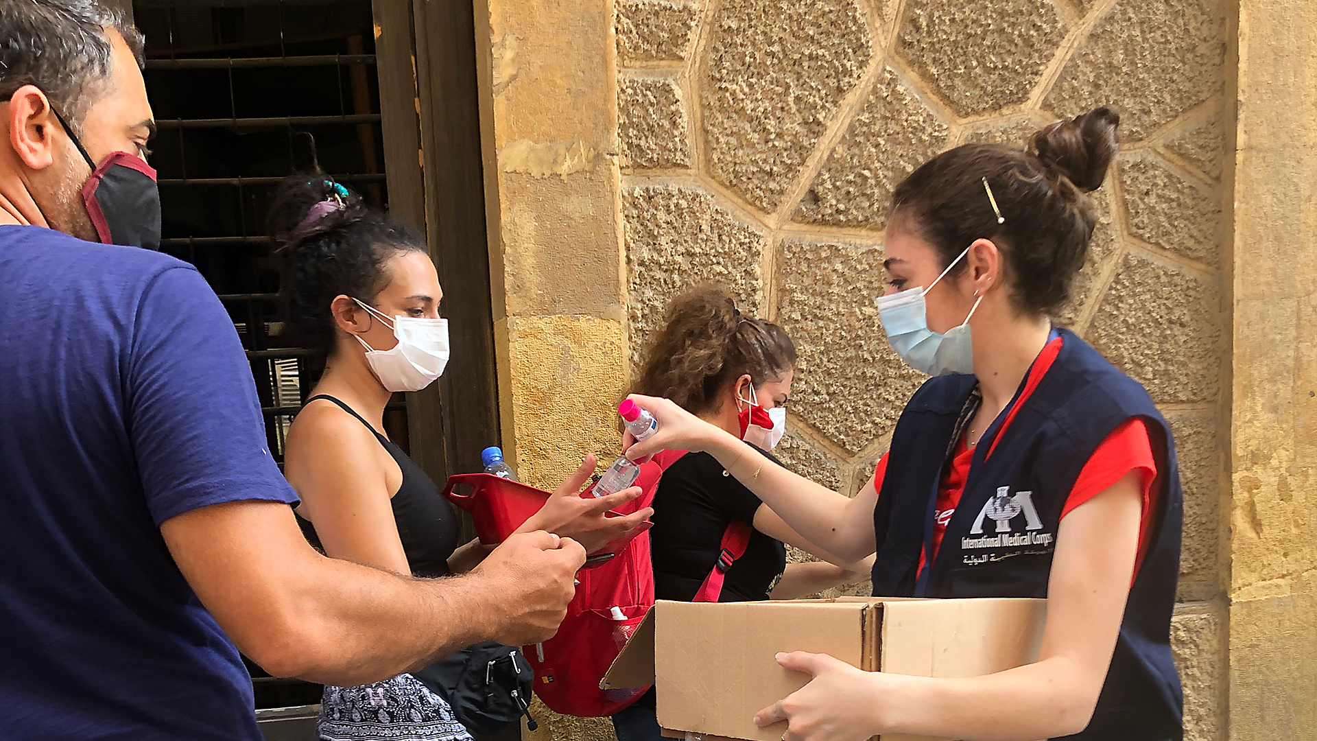 Lama, a disability officer for International Medical Corps, distributes hygiene supplies to volunteers who are cleaning up areas in Beirut affected by the port explosion. The supplies will help prevent COVID-19.
