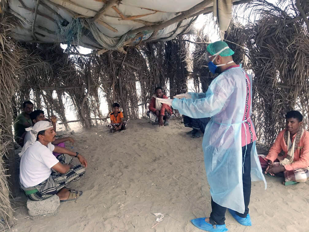 International Medical Corps physician and Yemen team Medical Officer Karam Showki talks with IDP camp residents in Hodeida Governorate about COVID-19.