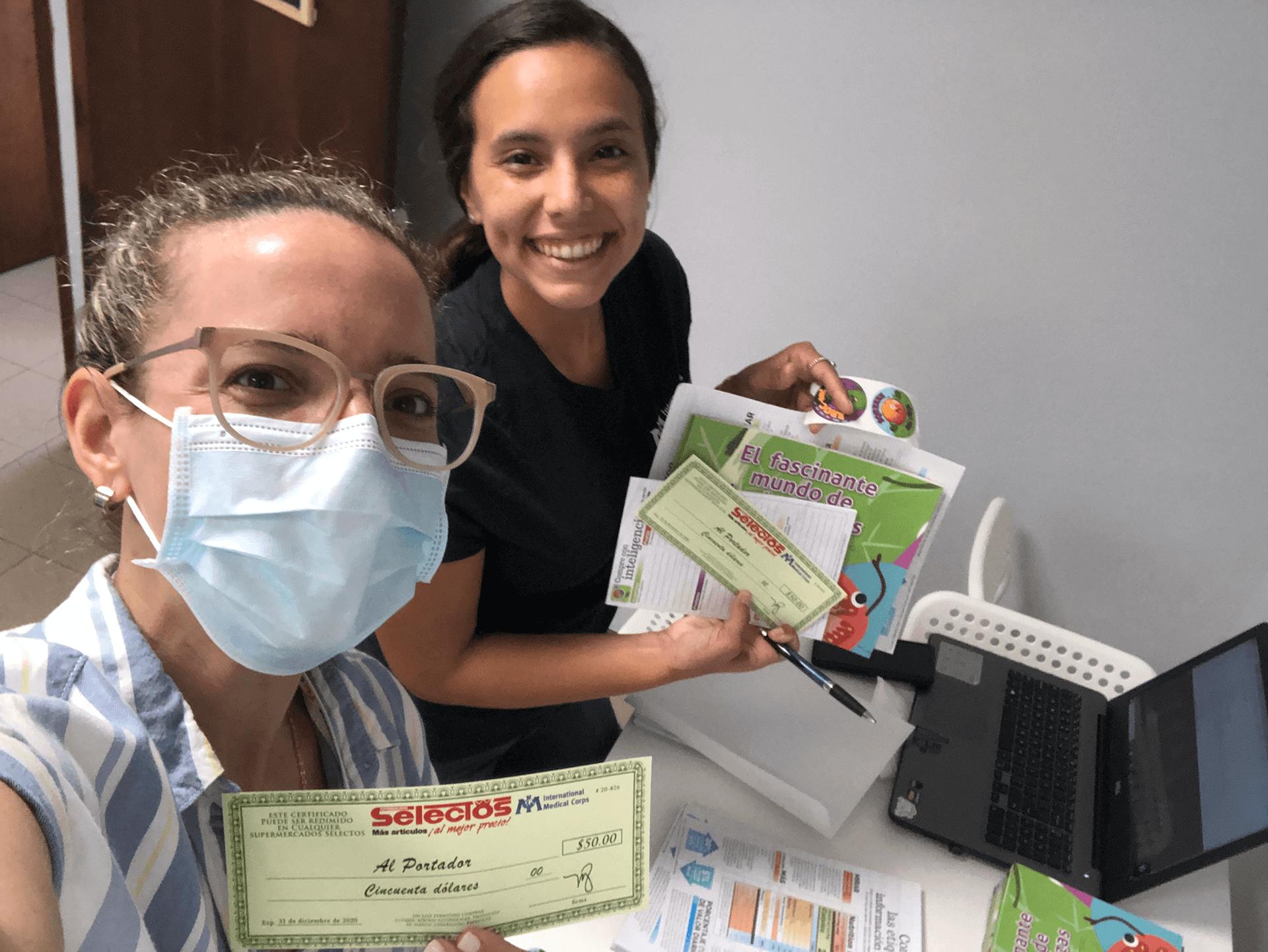 Suzanne Jimenez-Sanchez and Valeria Santa assemble food voucher kits.