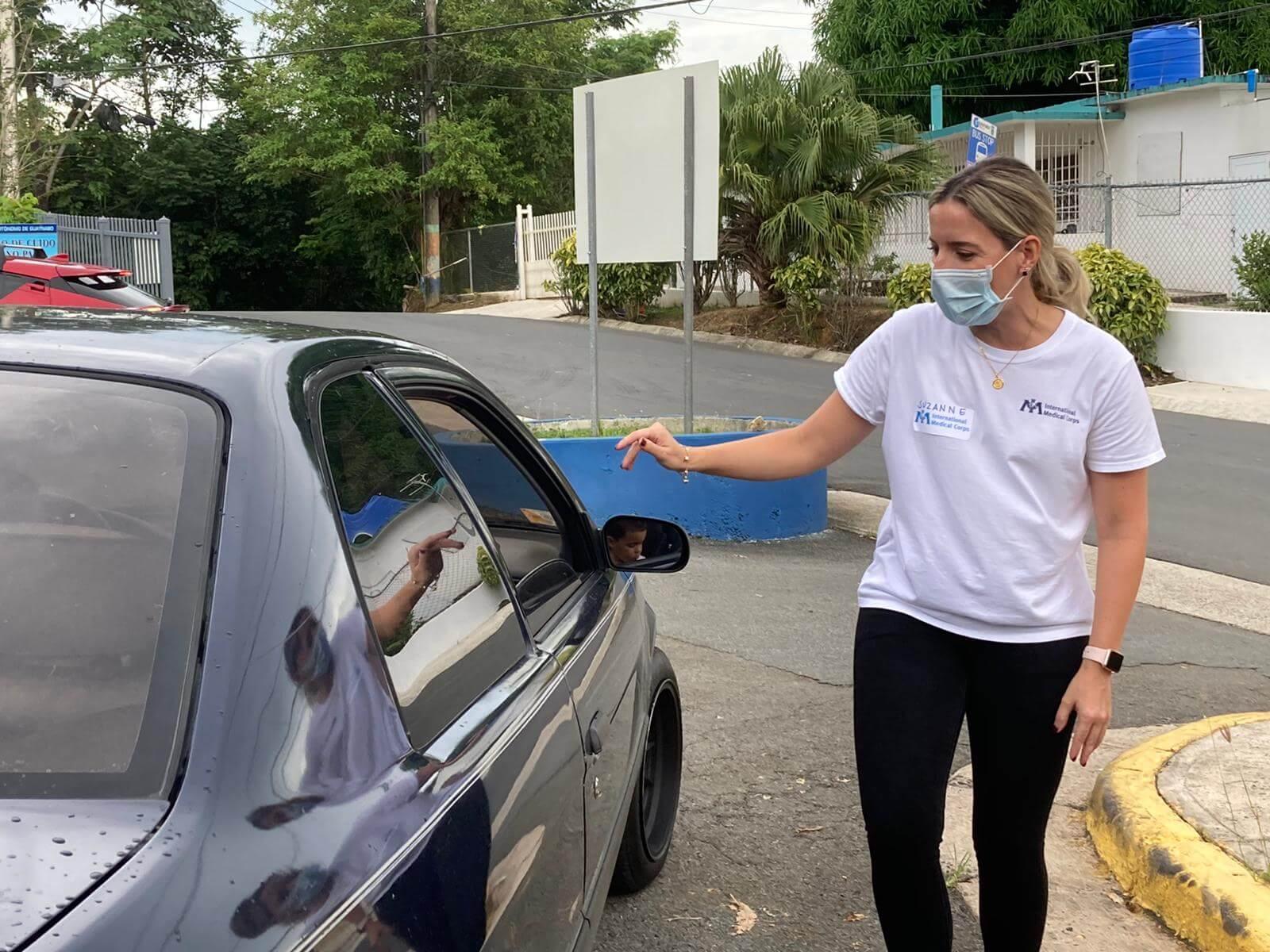 Suzanne Jimenez-Sanchez greets a family at the drive-through distribution site.