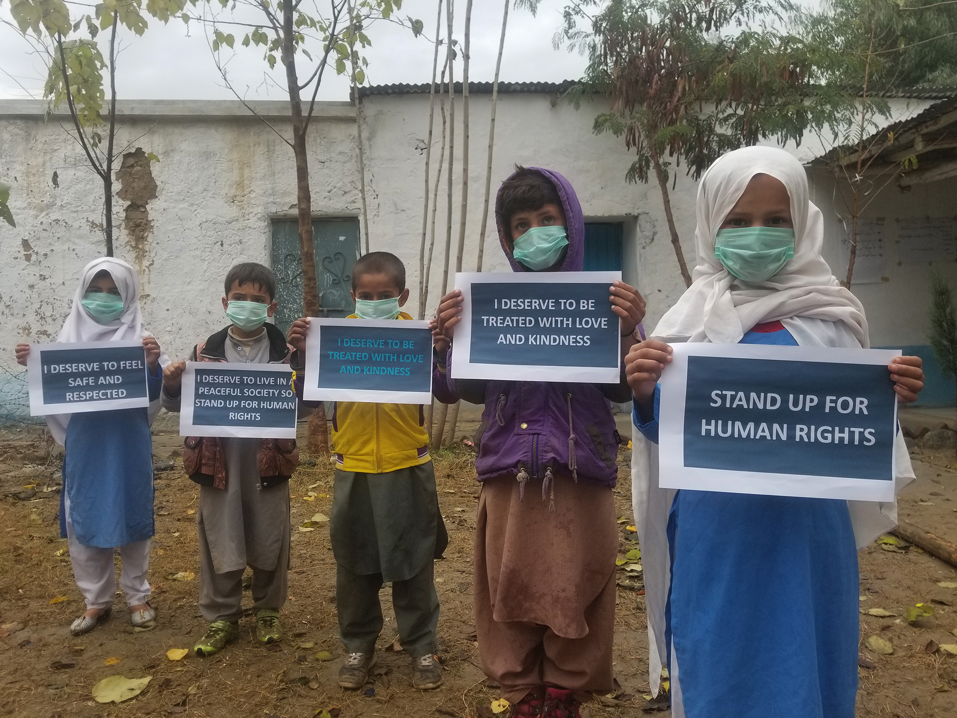 Young advocates in the Khyber Pakhtunkhwa province, Pakistan, carry signs to convey their messages on International Human Rights Day.