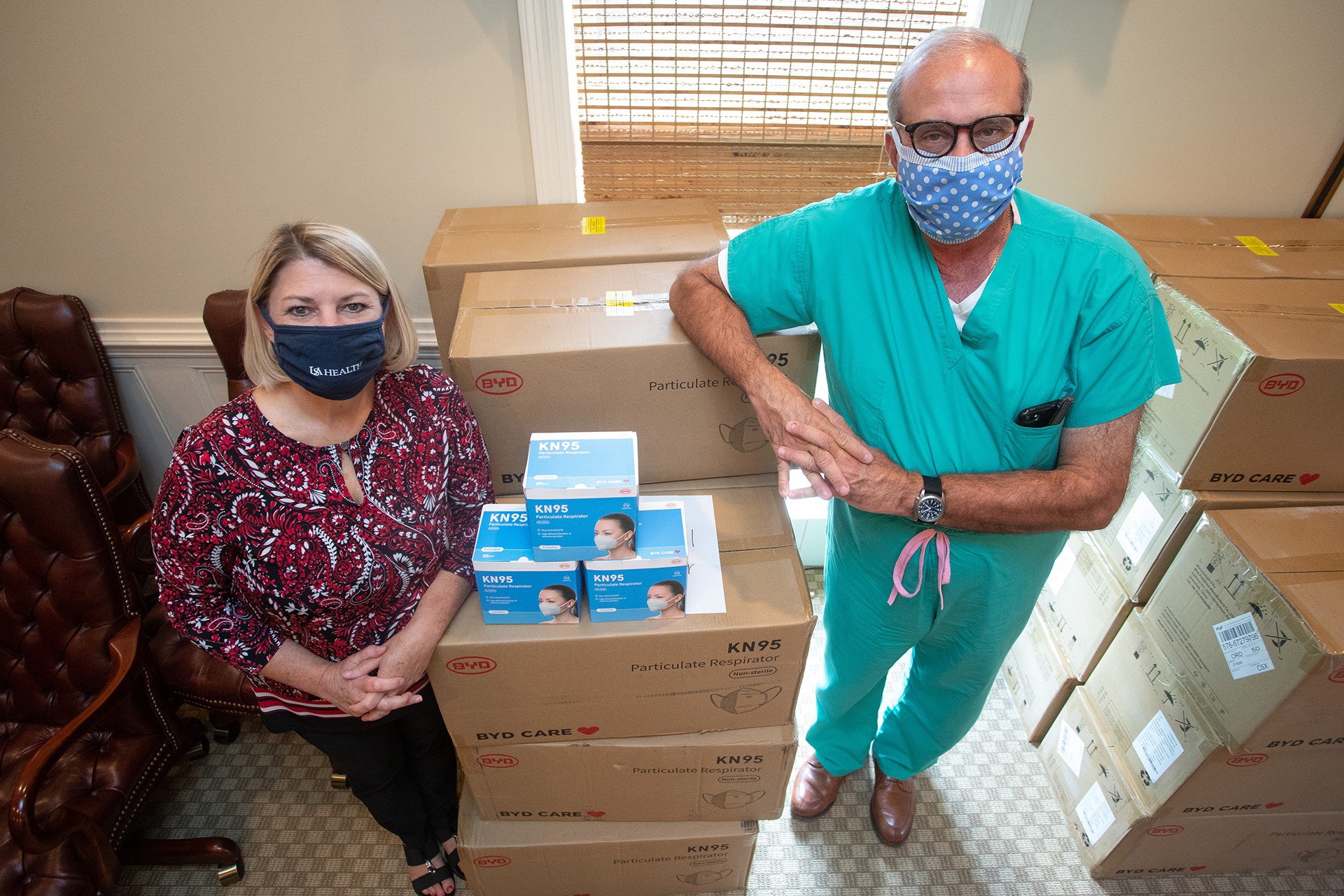 USA Health receives boxes of KN95 masks from the Medical Society of Mobile County, thanks to a donation from International Medical Corps. Pictured are Traci Jones, Senior Associate CFO and Assistant Vice President of Medical Affairs for USA Health, and Dr. George Koulianos, President of the Medical Society of Mobile County.