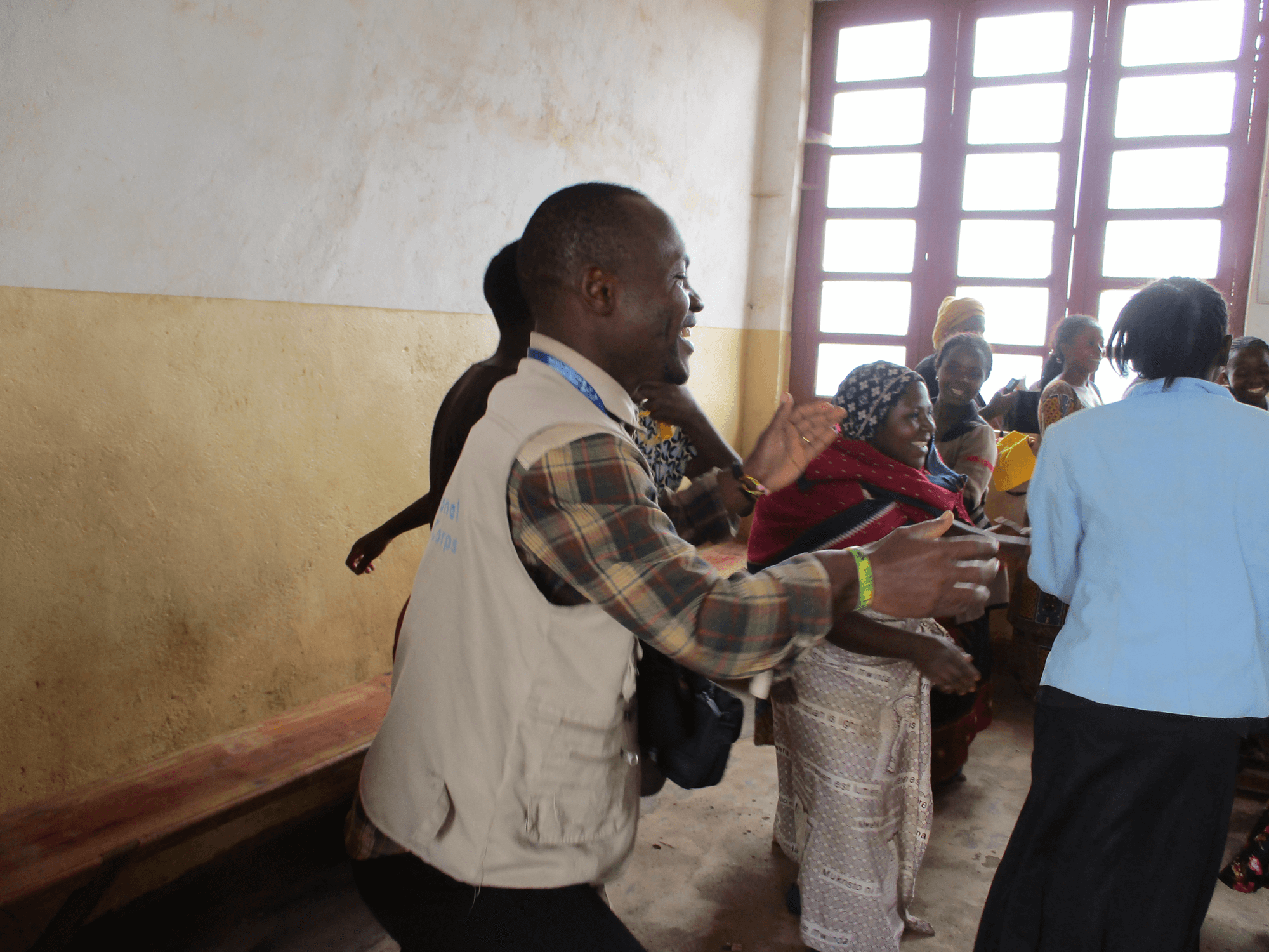 """Mussa celebrates with women in International Medical Corps' """"women's safe space,"""" which enables women at risk of gender-based violence to come together, receive support and learn new skills in North Kivu province, DRC."""