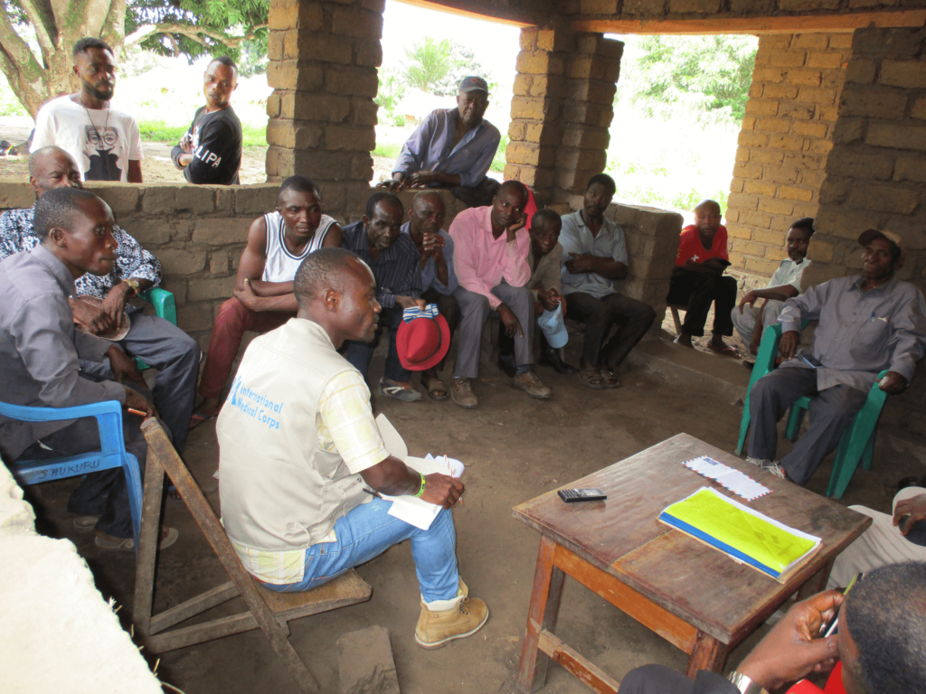 Mussa (lower left) helps lead a community meeting in Lumbwe village in South Kivu province.