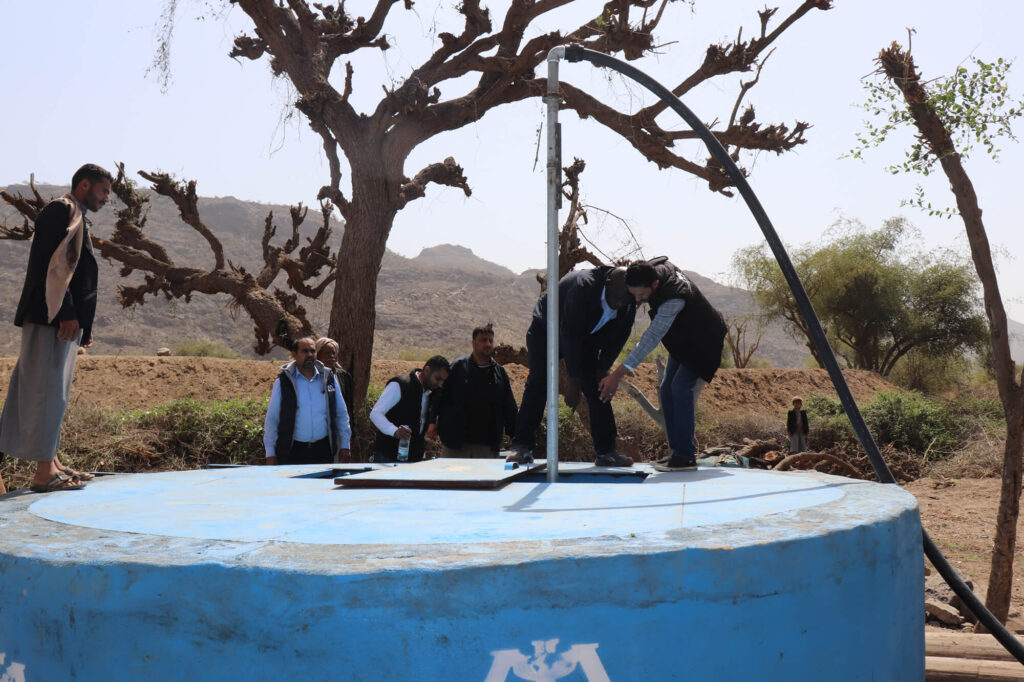 This covered water tank is part of a solar-powered water system in Sana'a governorate, Yemen. An uncovered and exposed well can spread waterborne diseases like cholera; a submerged pump and covered tank reduce disease risk.