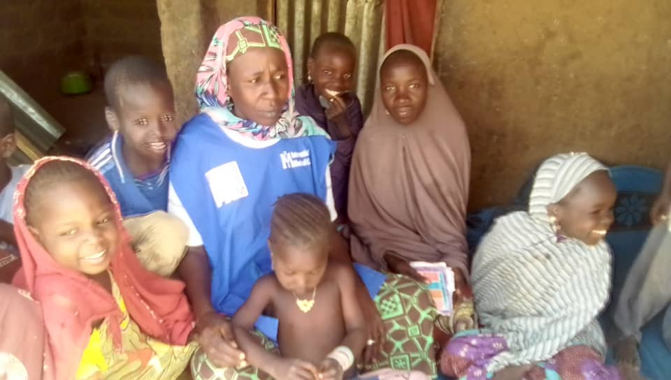 An International Medical Corps social worker visits Falmata (center) at her home to check on her after her surgery.
