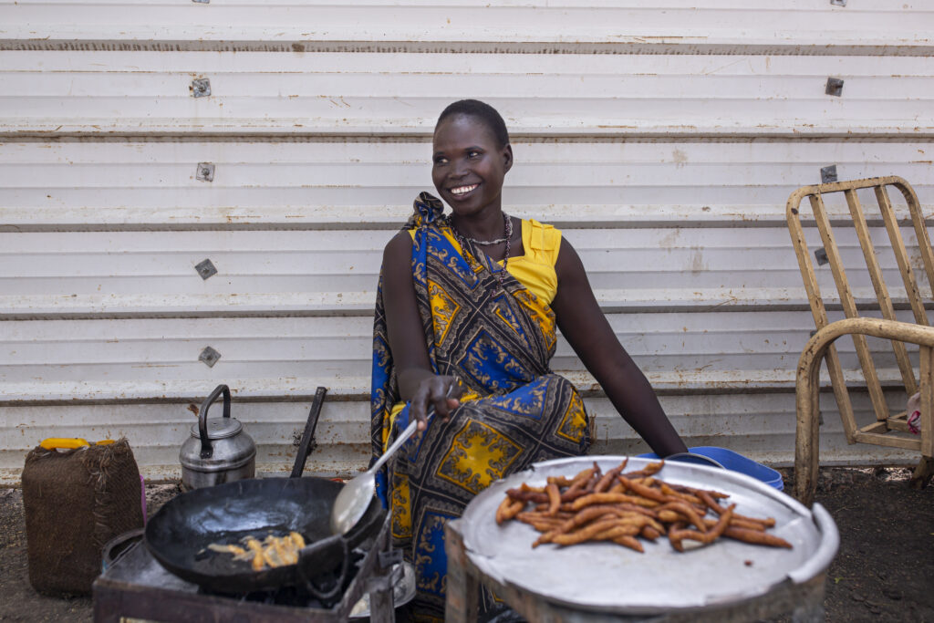 Nyabach John, 25, works at her food stand in Malakal, South Sudan, on March 19, 2021.