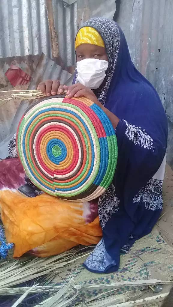 Maryan Abdi Mohammed weaves a colorful basket that she will sell in the local market. She makes baskets, mats and hats, and her business is profitable, bringing meaningful income to her family.