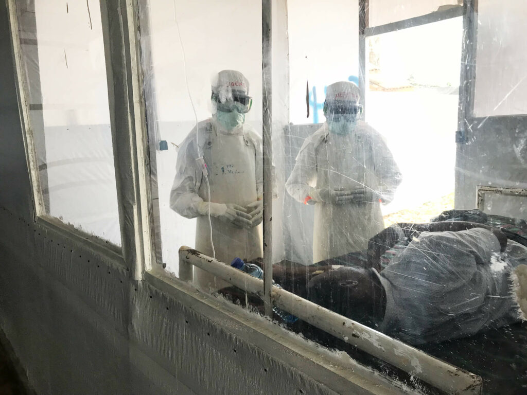 Staff check on a patient in the Mangina Ebola Treatment Center in North Kivu province, DRC.