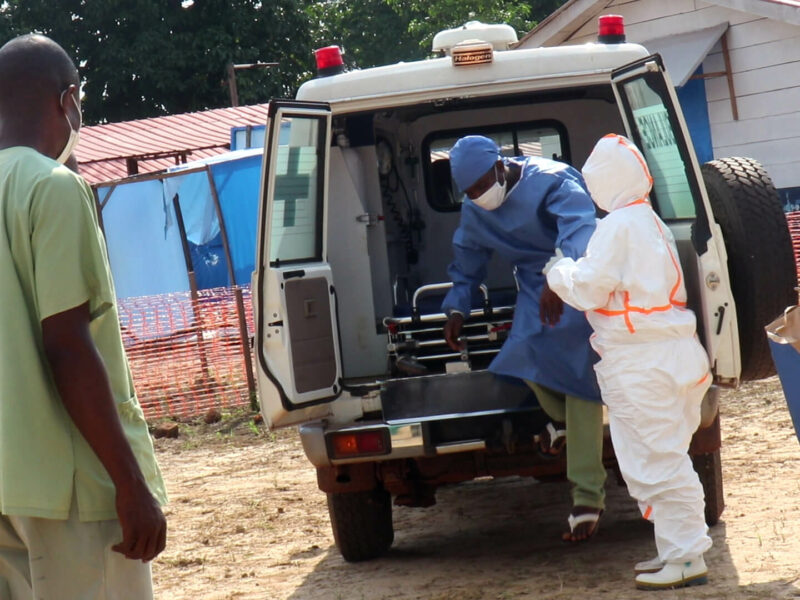 Nurses help a patient with a suspected case of Ebola to get out of an ambulance at Wangata Ebola Treatment Center in Équateur Province, DRC.