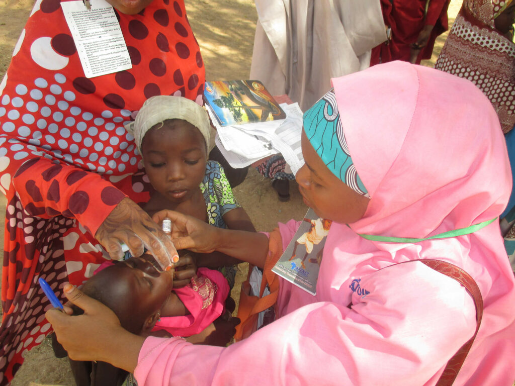 A polio eradication worker administers an oral polio vaccine to a child in Nigeria.