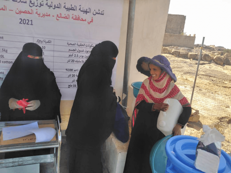Members of our staff distribute hygiene kits to residents of Al-Hussain District in Al-Dhale Governorate. In this photo, a grateful resident tucks a new plastic jerry can—part of each kit—under her arm.