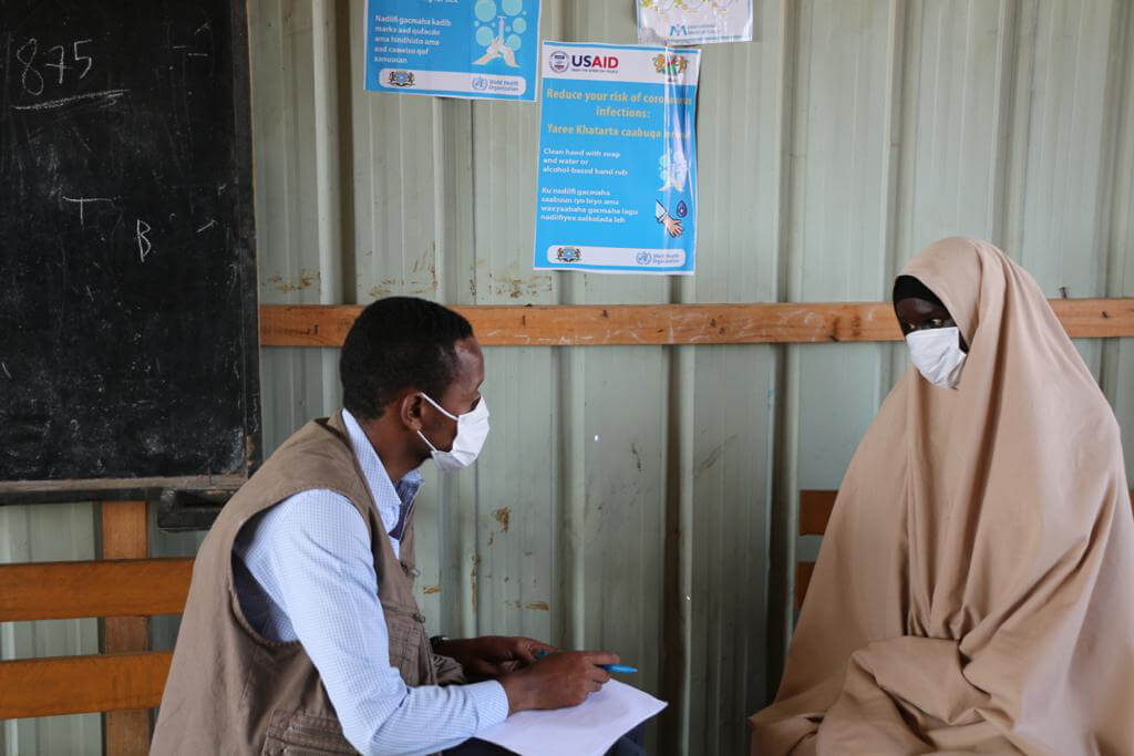 Hawo Aliyow (right) discusses the COVID-19 pandemic with an International Medical Corps staff member.