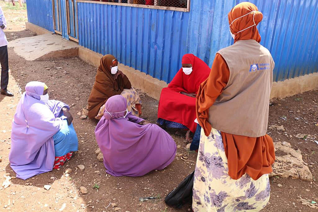 Rowly Humow (standing) shares information about how to prevent COVID-19, and what the signs and symptoms of the virus are, with women at Banow IDP camp.