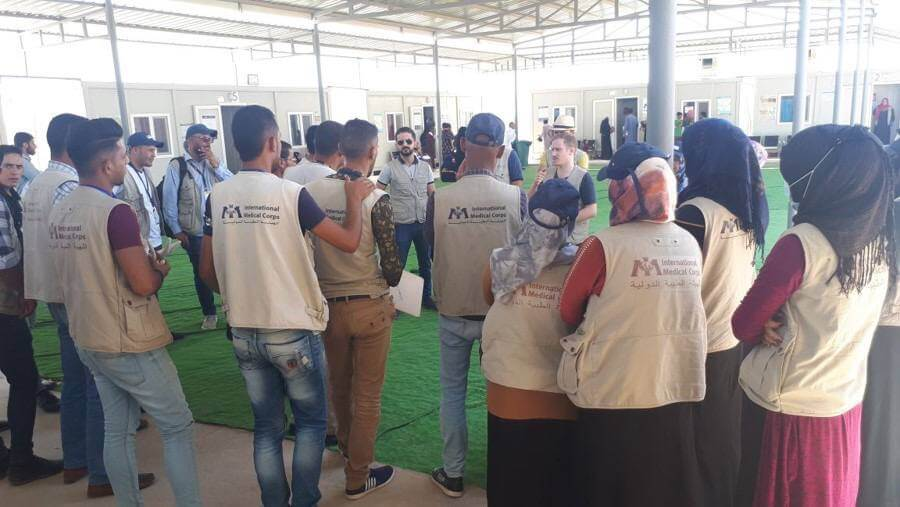 Dr. Furat (center) during a July 2018 orientation for community health workers at the start of a scabies prevention campaign in Hammam al-alil camp.