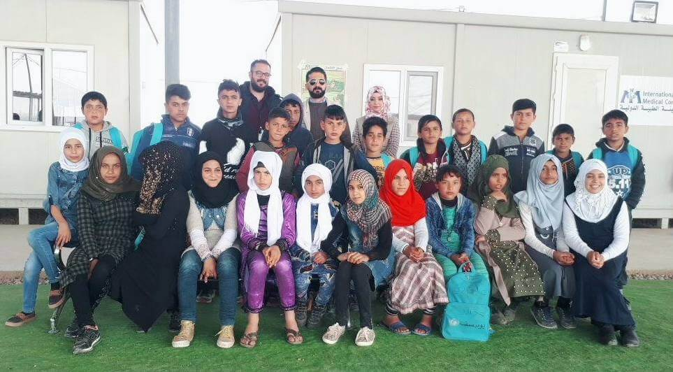 Dr. Furat (center, top) with a team of junior community health workers in Hammam al-alil camp.