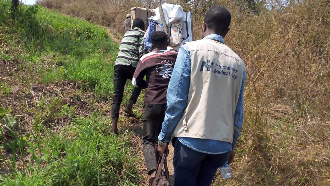 Community health workers together with International Medical Corps staff transport medical equipment by foot to the health center in Fizi, South Kivu province.