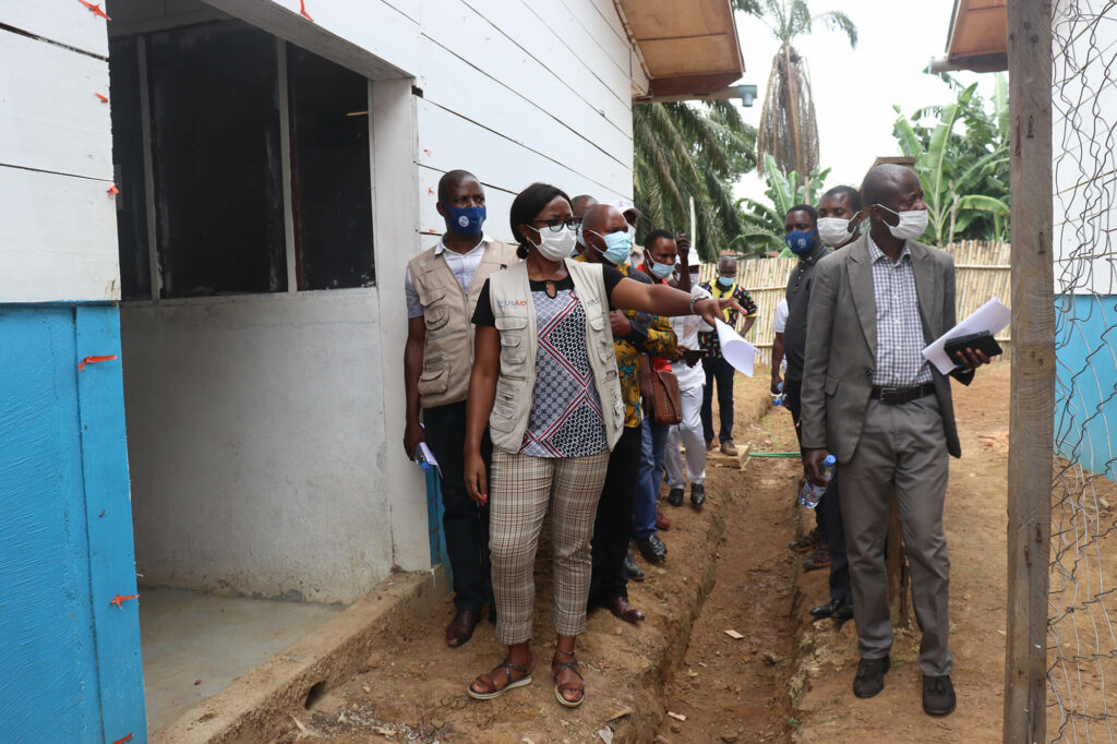 An International Medical Corps nurse supervisor shows local leaders and community members the Ebola treatment center in Bikoro, Équateur province.