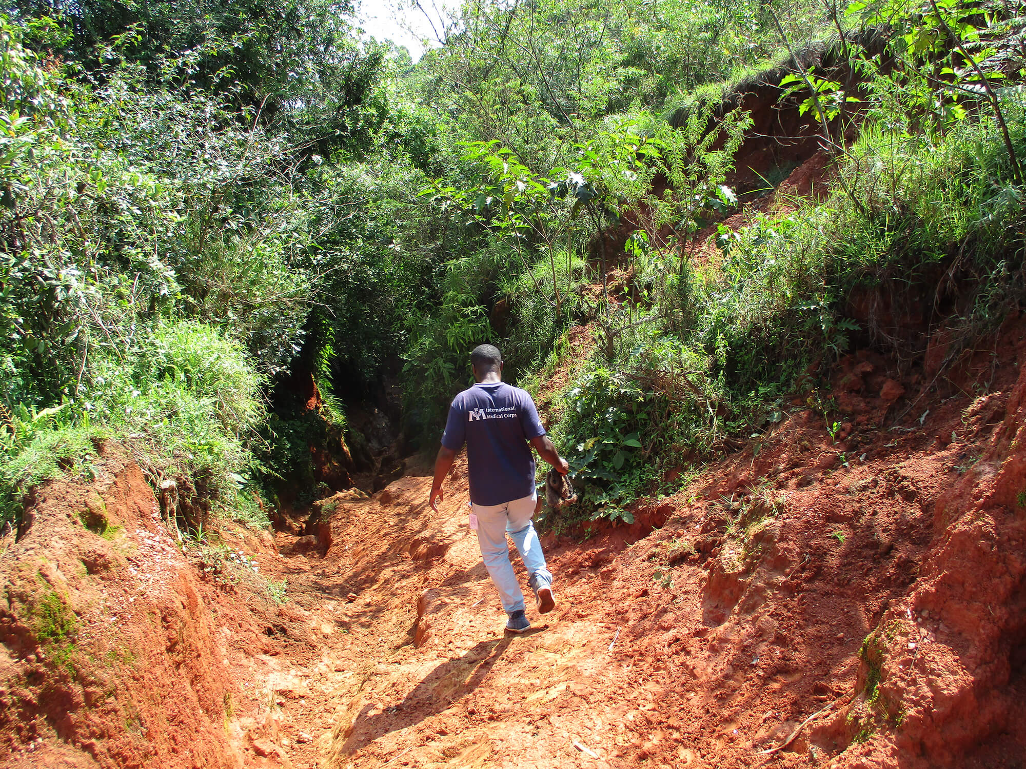 During a health assessment in South Kivu province, International Medical Corps staff travel by foot along the road to Itombwe village.