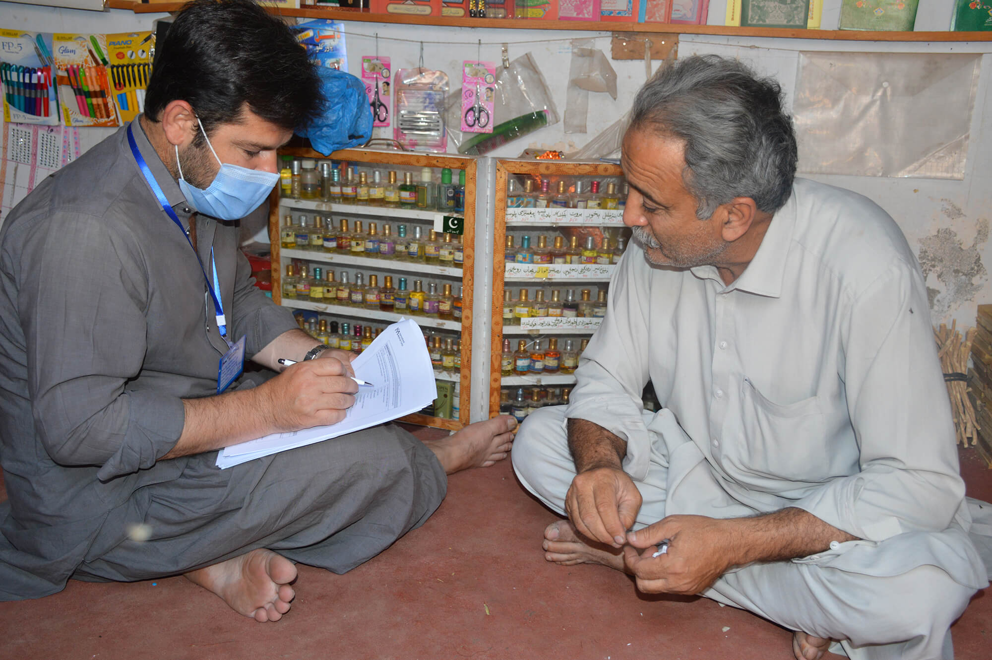 A data collector interviews a male community member.