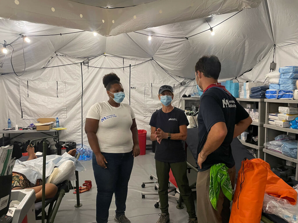 Sue Mangicaro (center) speaks with John Roberts (right) and Vanessa Delone Jean Louis inside the EMT.
