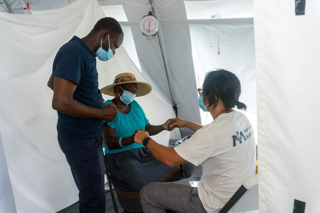 Volunteer doctor Alex Wang treats a Haitian woman with the help of a local translator, Yacinthe Venord.